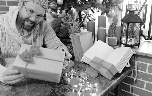 古い本とテーブルにクリスマスプレゼントを書くひげの男