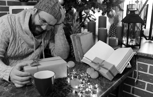 Beard man writing christmas gifts on a table with old books