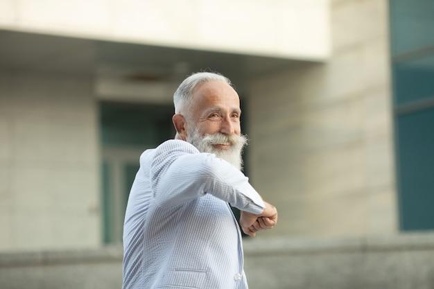 ひじで挨拶するひげの年配の男性
