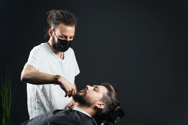 理髪店で髭剃り。黒の医療用マスクのドレッドヘアを持つ床屋は、検疫コロナウイルスcovid-19でひげを生やした男をトリミングします。