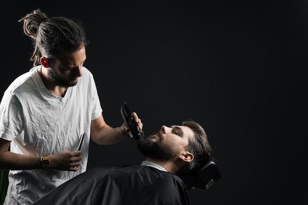 理髪店で髭剃り。ドレッドヘアの床屋はハンサムなひげを生やした男をトリミングします。
