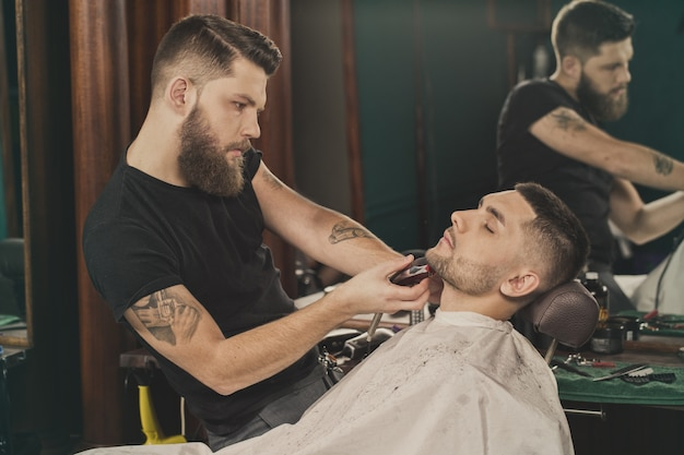 Beard styling. horizontal portrait of a barber shaping beard of his client using a trimmer