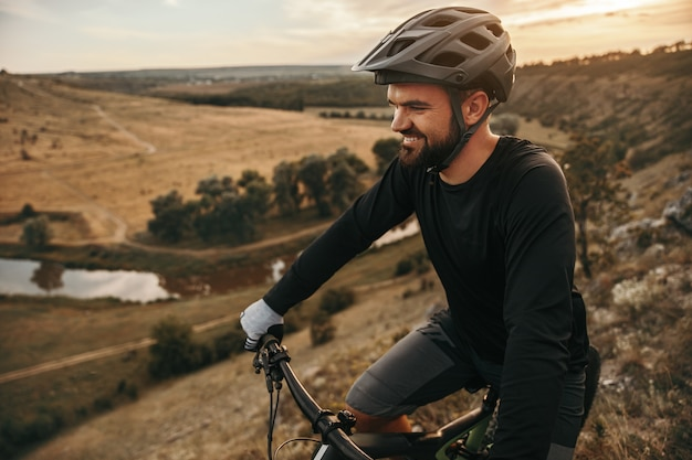 Bearded adult cyclist riding bicycle through hilly terrain