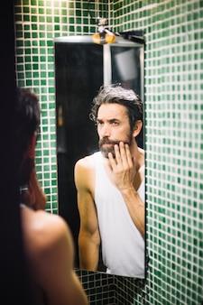 Бородатый взрослый человек смотрит на стекло