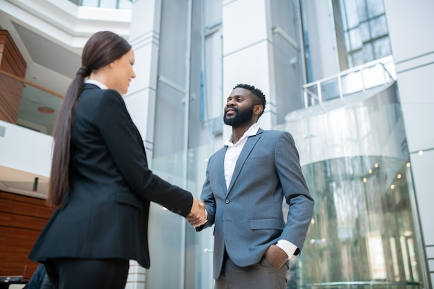 Bearded afro-american businessman in suit shaking hand of colleague while congratulating her with successful contract