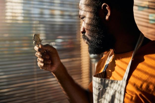 Бородатый афроамериканец держит портативный триммер для волос