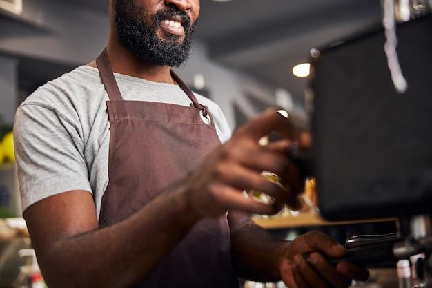 Бородатый афроамериканец готовит эспрессо с кофеваркой