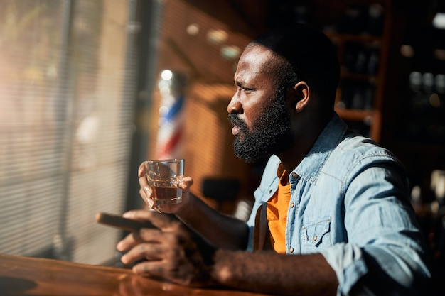 Bearded afro american man smoking cigar and drinking whisky