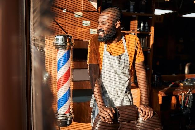 理髪店の窓のそばに立っているひげを生やしたアフリカ系アメリカ人の男