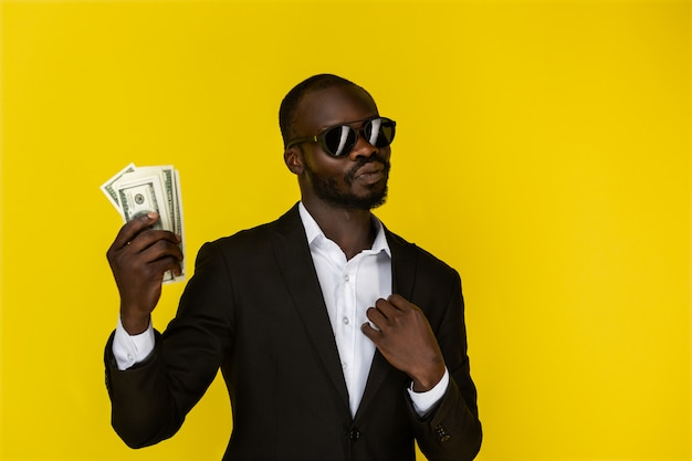 Bearded afroamerican guy is holding dollars in one hand, wearing sunglasses and black suit