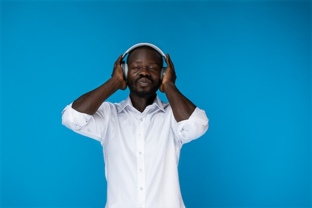 Bearded afroamerican man with closed eyes is in big headphones in white shirt