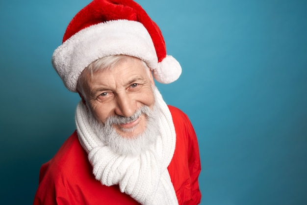 Uomo anziano barbuto in costume rosso natalizio e sciarpa bianca