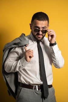Бородатый и серьезный деловой человек, одетый в сероватый люкс, позирует, держа куртку на плече, вешая ее за спиной, глядя на опускающиеся солнцезащитные очки, изолированные на желтом фоне.