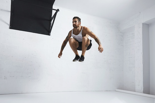 ひげを生やした入れ墨の若い男性アスリートは、美容体操の動きを示していますフィットネスセンターの白い部屋で隔離された空中でのハイジャンプ