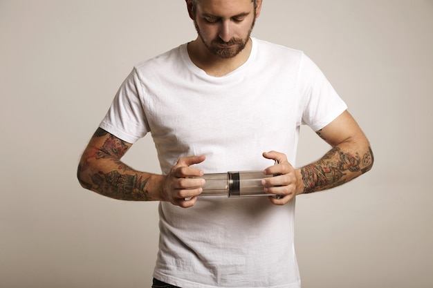 빈 밝은 회색 명확한 aeropress를 들고 빈 흰색면 티셔츠에 수염과 문신을 한 젊은 남자