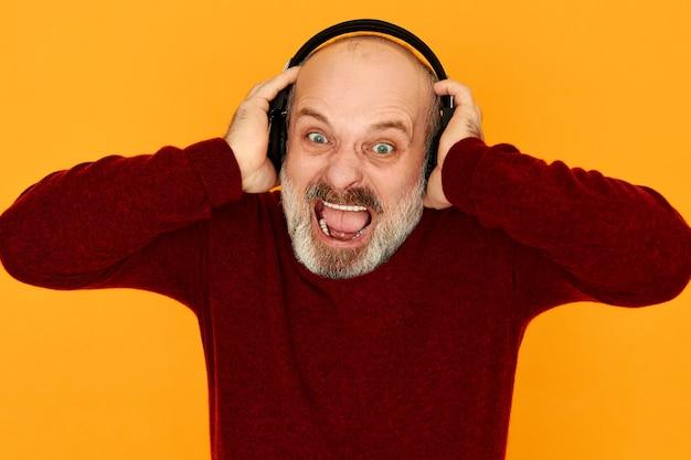 Barbuto arrabbiato uomo in pensione furioso in maglione lavorato a maglia che apre la bocca ampiamente infuriato con cattive notizie ascoltando la stazione radio sportiva tramite cuffie bluetooth senza fili, urlando ad alta voce