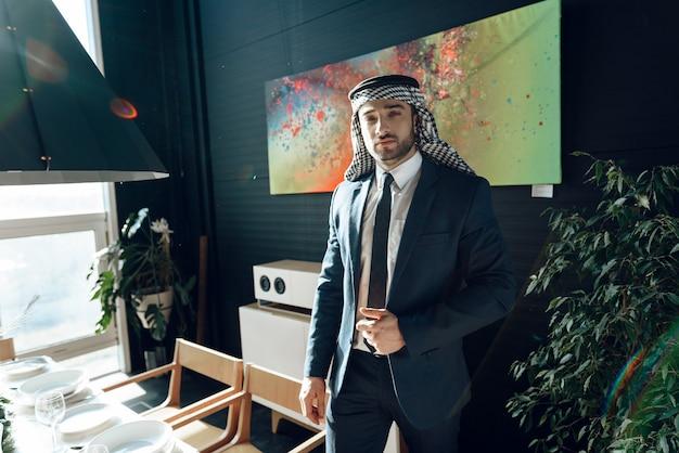 Bearded arab businessman in suit standing near dinner table.