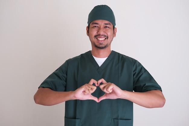 수염을 기른 아시아 간호사 남자는 친절하게 웃고 손가락을 사용하여 사랑의 심장 모양을 제공합니다.
