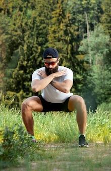 일몰에 야외 체육관에서 운동 운동을 하 고 수염 된 운동 남자.