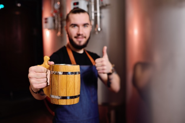 Bearded attractive male brewer with wooden beer mug in hand on background of brewery
