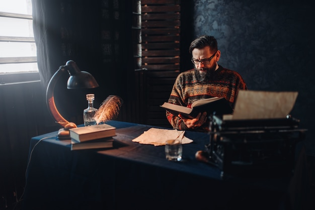 Bearded author in glasses reading a book