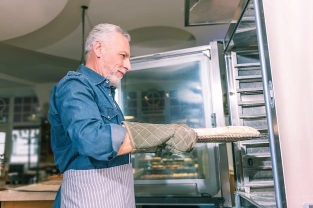ひげを生やしたパン屋。縞模様のエプロンを身に着けているひげを生やした白髪のパン屋は、オーブンにパイとトレイを置きます