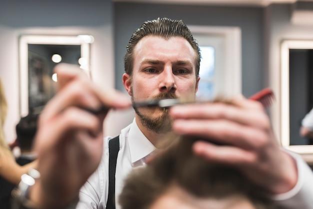 Barbiere barbuto che taglia i capelli al cliente