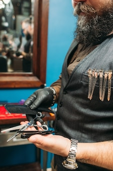 散髪ツールを保持しているひげを生やした床屋