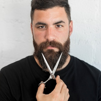 Bearded barber holding scissors at hair salon