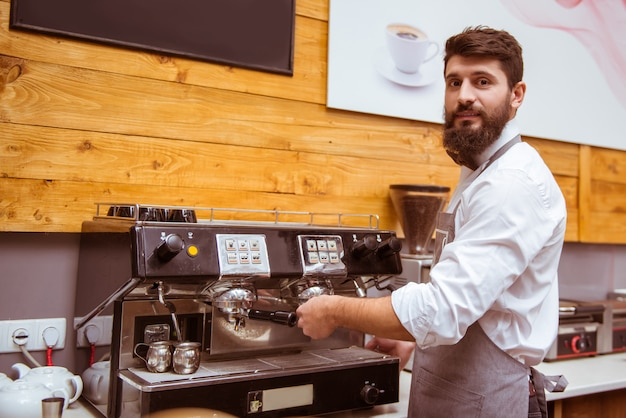 Bearded barista makes coffee for a client.