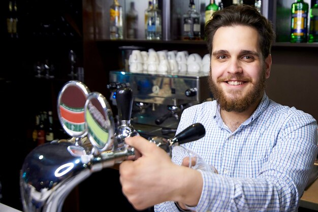 A bearded barman with a smile pours beer into the glass.
