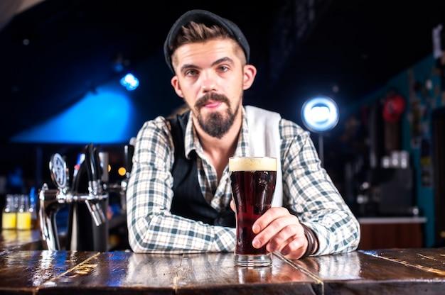 Бородатый бармен создает коктейль, стоя возле барной стойки в баре