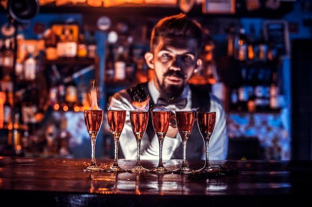ひげを生やしたバーテンダーがナイトクラブのバーカウンターの近くに立っている間、飲み物を注いでいます