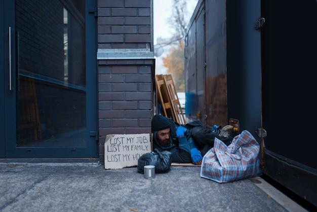 Bearded beggar sleeping on city street.