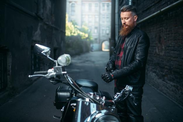 Бородатый байкер в кожаной одежде против чоппера