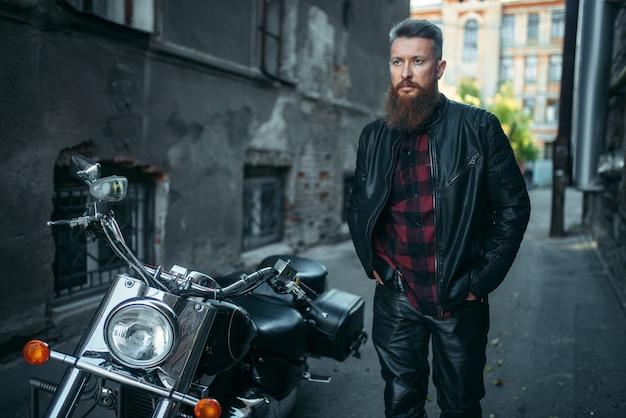 Бородатый байкер в кожаной одежде против своего вертолета.