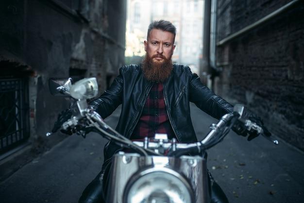 Бородатый байкер в кожаной куртке сидит на классическом чоппере
