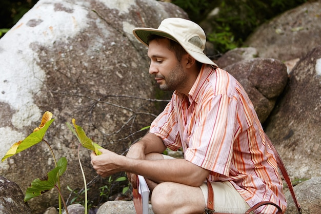 Bearded biologist wearing hat sitting among rocks and holding leaves of green plant with spots, looking with concerned expression while examining them for diseases, conducting environmental studies