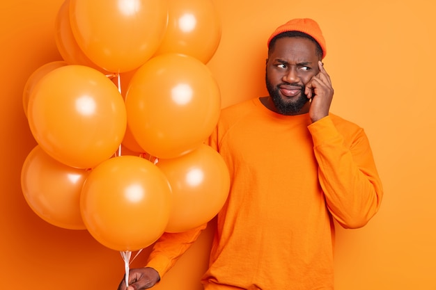 Bearded black man considers something with puzzled expression keeps hand on temple tries to think how organize birthday party dressed in casual bright clothes holds bunch of inflated balloons