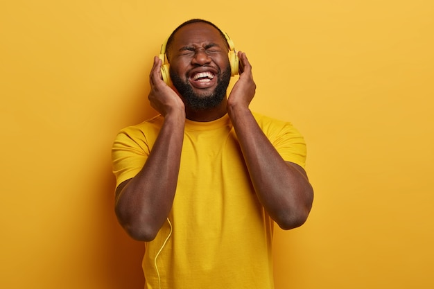 Bearded black man fascinated with nice quality of headphones, listens pleasant music, connected to some electronic device