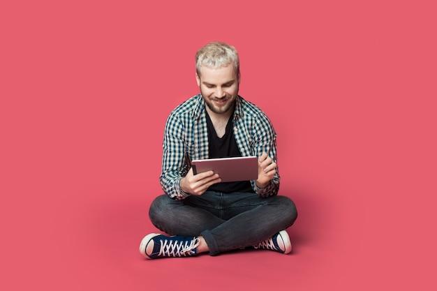 ひげを生やした金髪の男は、赤いスタジオの壁に笑みを浮かべて床にタブレットを使用しています