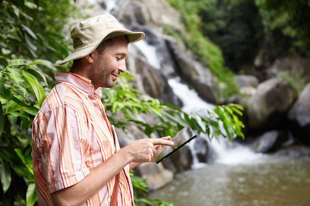 Bearded botanist wearing panama hat using digital tablet pointing at blank screen with happy expression, standing at mountain river against waterfall while conducting water analysis