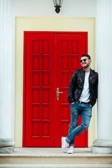 Бородатый мальчик с красивой улыбкой позирует на фоне красной двери