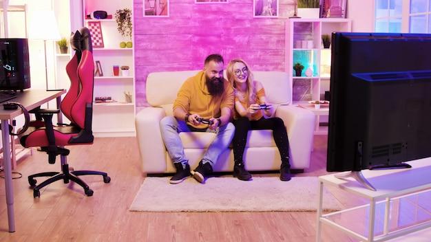 수염난 남자친구가 무선 컨트롤러를 사용하여 소파에 앉아 아름다운 금발 여자친구와 온라인 게임을 하고 있습니다.