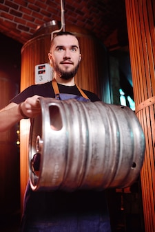 A bearded brewer in an apron holds a metal keg with beer in his hands and smiles