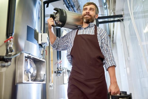 Bearded brewer with beer kegs