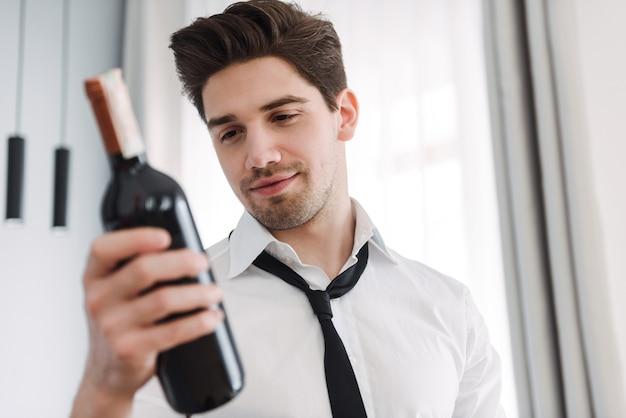 호텔 아파트에서 와인 한 병을 들고 공식적인 옷을 입고 수염 갈색 머리 사업가