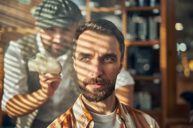A bearded brunette client of a barbershop getting his hair groomed