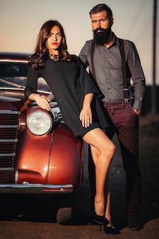 シャツとサスペンダーのズボンでひげを生やしたブルネットの男は、暗いフィールドの背景に茶色のレトロな車の近くに黒のショート ドレスで長い髪の細い若い女の子を抱きしめます