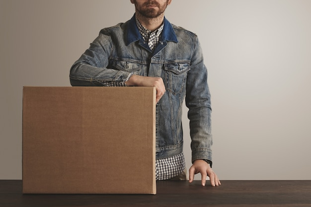 Bearded brutal courier in jeans work jacket stays near presented big carton paper box with goods on wooden table.